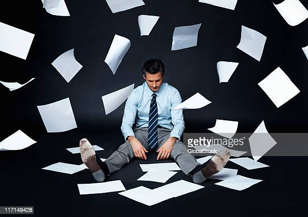 Businessman sitting on a dark surface with papers flying