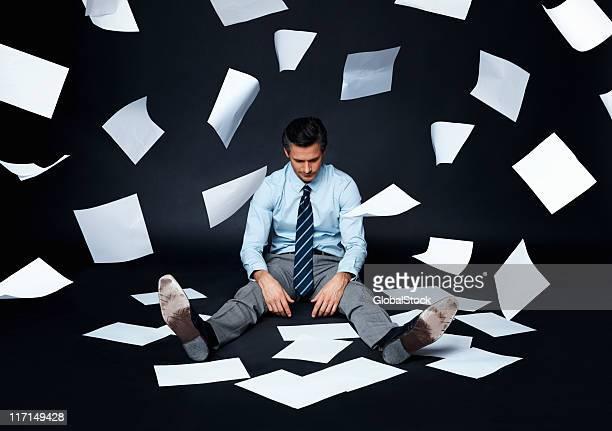 businessman sitting on a dark surface with papers flying - förstoring bildbanksfoton och bilder