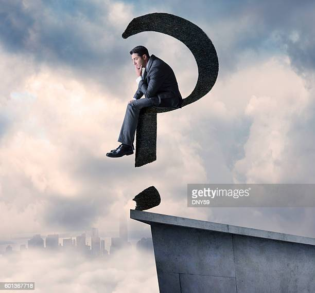 Businessman Sitting On A Floating Question Mark High Above City