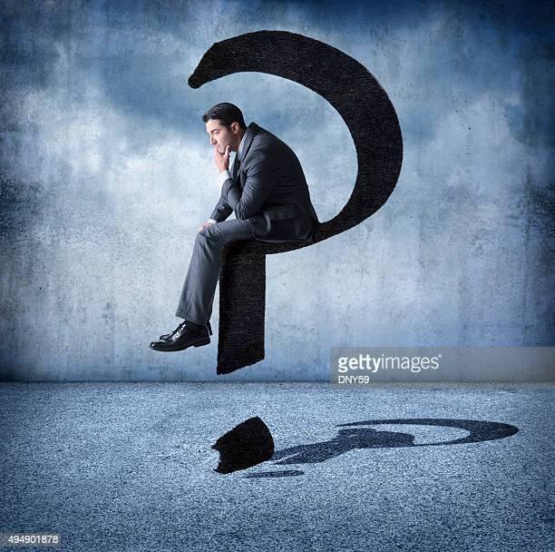 Empresário sentado em um ponto de interrogação flutuante