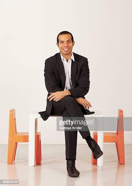 businessman sitting on a miniature table sweden. - mid adult men imagens e fotografias de stock