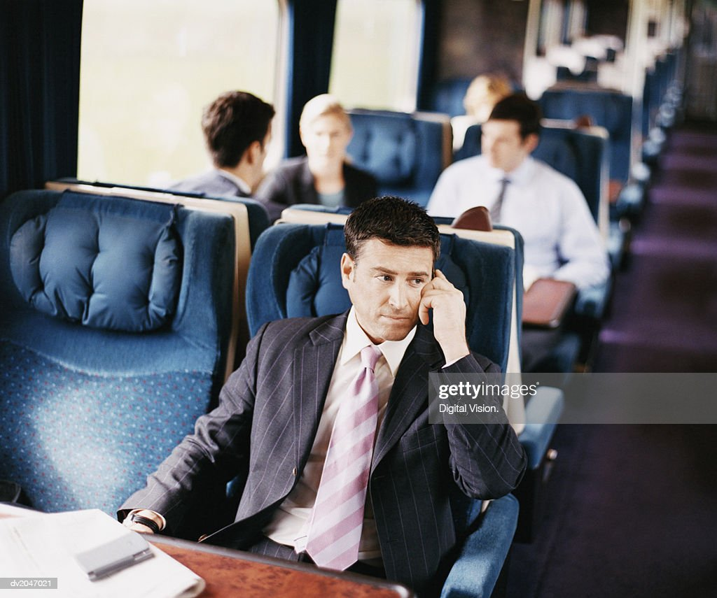 Businessman Sitting on a Passenger Train With His Hand on His Head : Stock Photo