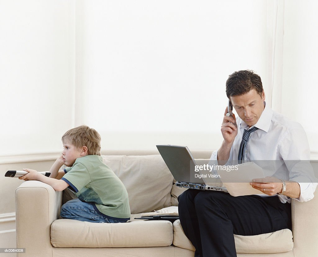 Businessman Sitting on a Sofa at Home With a Laptop and Using a Mobile Phone and His Son Watching TV : Stock Photo