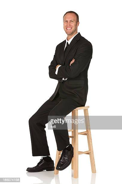 Businessman sitting on a stool and smiling