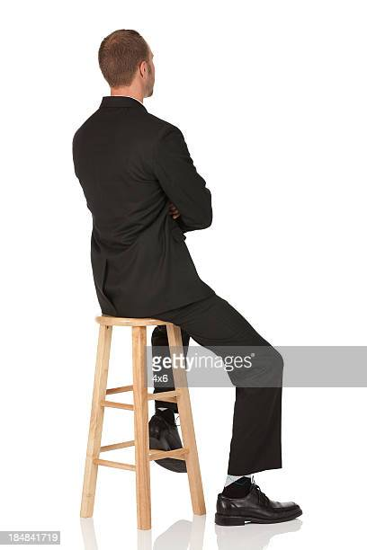 Homme d'affaires, assis sur un tabouret