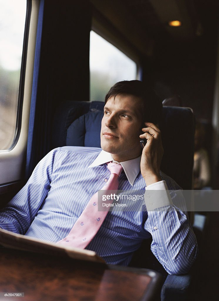 Businessman Sitting on a Train and Using His Mobile Phone : Stock Photo