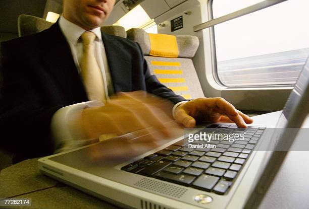Businessman sitting on a train working on a laptop computer