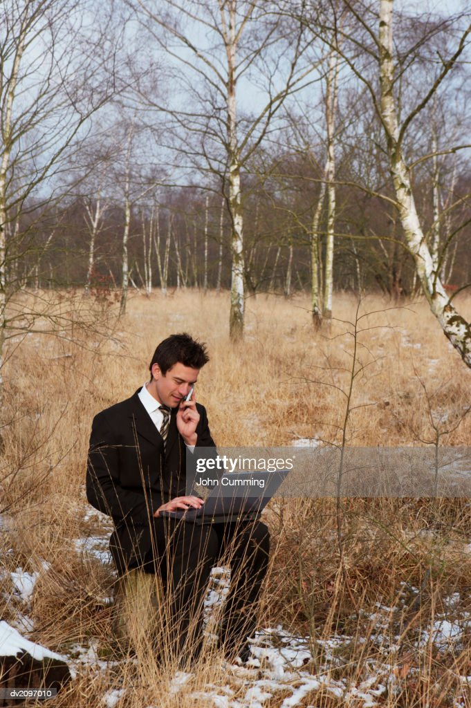 Businessman Sitting on a Tree Stump in the Woods Using His Mobile Phone and a Laptop : Stock Photo