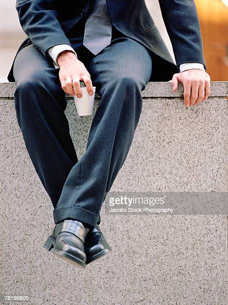 Businessman sitting on a wall
