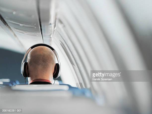 Businessman sitting on aeroplane seat, wearing headphones, rear view