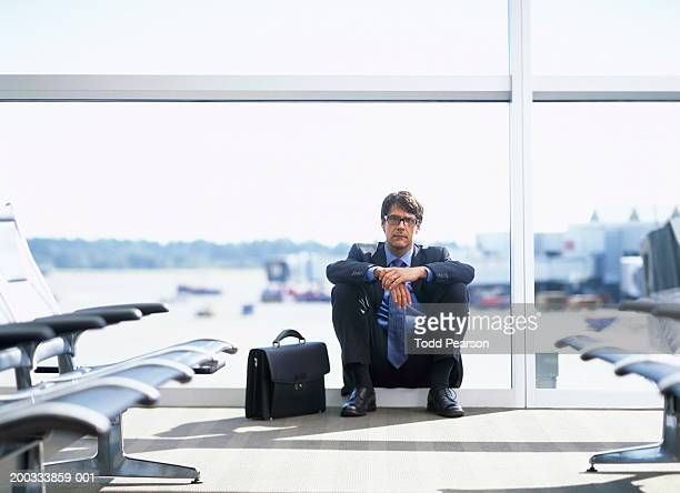 Businessman sitting on airport window sill near briefcase