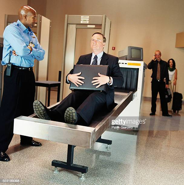 businessman sitting on airport x-ray - security scanner stock pictures, royalty-free photos & images