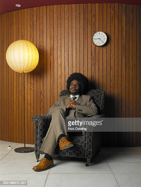 businessman sitting on armchair - big hair stock pictures, royalty-free photos & images