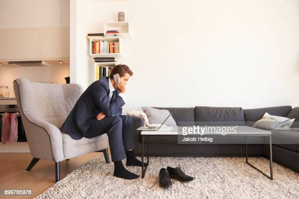 Businessman sitting on armchair using laptop and making smartphone call