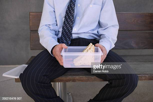 Businessman sitting on bench holding sandwich box, mid section