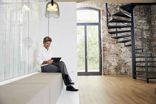 Businessman sitting on bench in modern office using tablet - gettyimageskorea