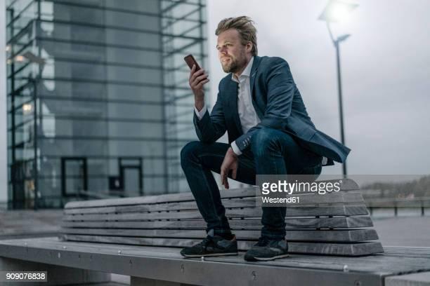 businessman sitting on bench in the city holding cell phone - sitzbank stock-fotos und bilder