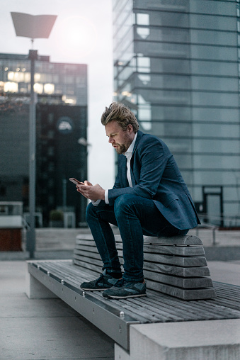 Businessman sitting on bench in the city using cell phone - gettyimageskorea