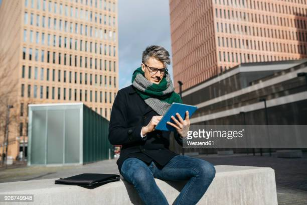 businessman sitting on bench in the city using tablet - independência imagens e fotografias de stock