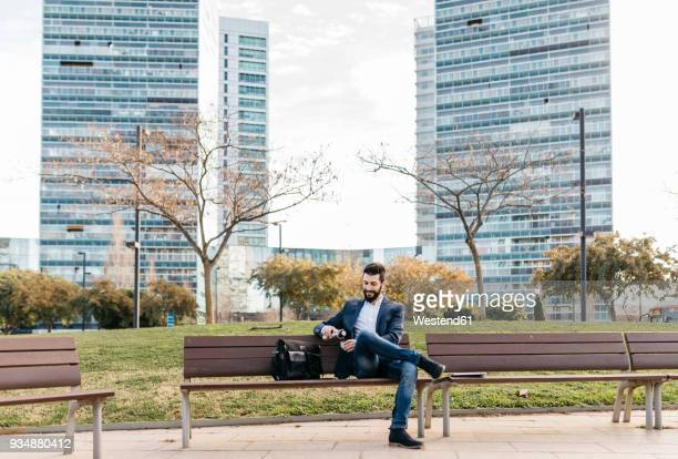 businessman sitting on bench outside office building drinking coffee - ベンチ ストックフォトと画像