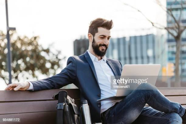 businessman sitting on bench outside office building using laptop - freischaffender stock-fotos und bilder