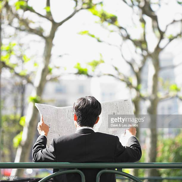 Businessman sitting on bench reading newspaper