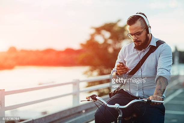 Businessman Sitting On Bicycle And Using Smartphone Outdoors.