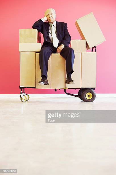 Businessman Sitting on Boxes