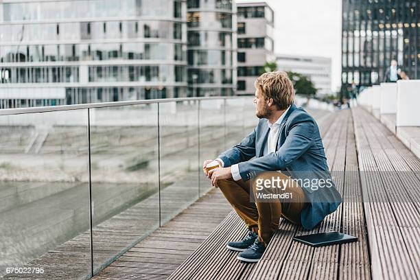 Businessman sitting on bridge having coffee break