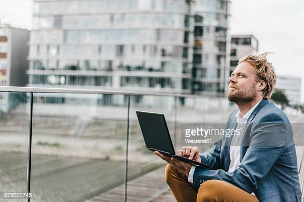businessman sitting on bridge using laptop looking up - outdoors stock-fotos und bilder