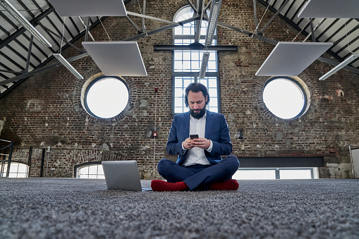 Businessman sitting on carpet in a loft using cell phone - gettyimageskorea