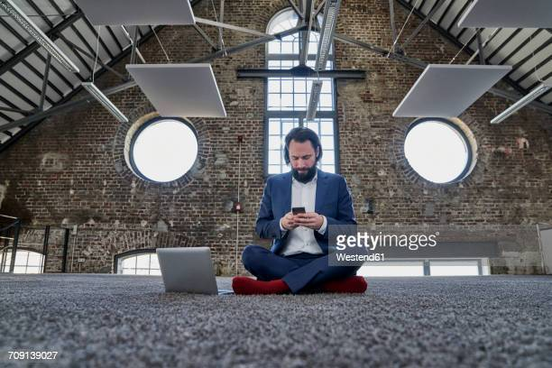 Businessman sitting on carpet in a loft using cell phone
