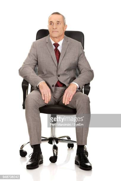 Businessman Sitting On Chair Against White Background