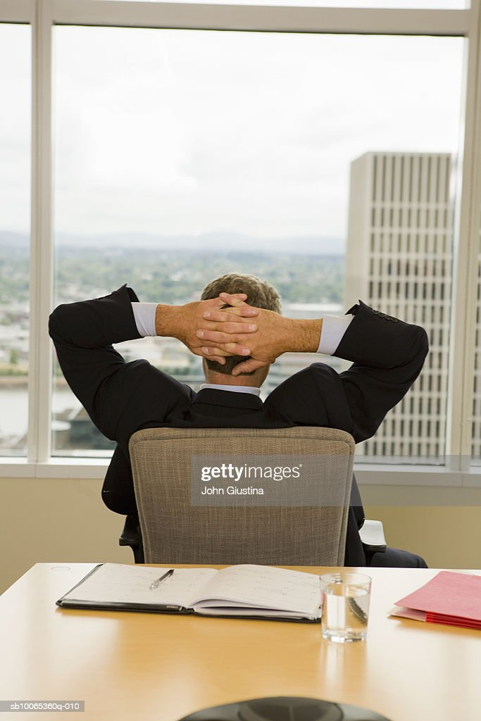 Businessman sitting on chair, looking through window, rear view : Foto stock