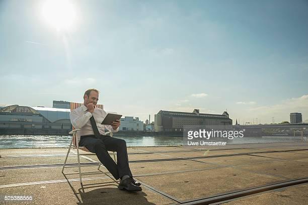 Businessman sitting on chair on tram tracks using tablet