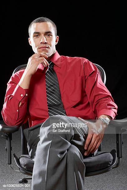 Businessman sitting on chair, portrait, close-up