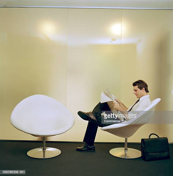 Businessman sitting on chair, reading newspaper, side view