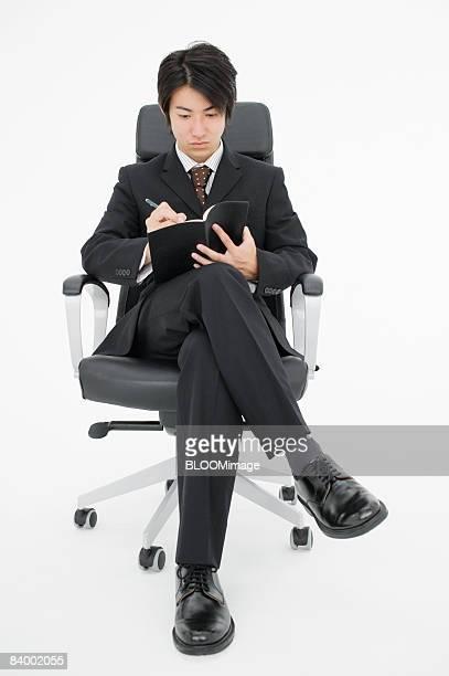 Businessman sitting on chair, taking notes, studio shot