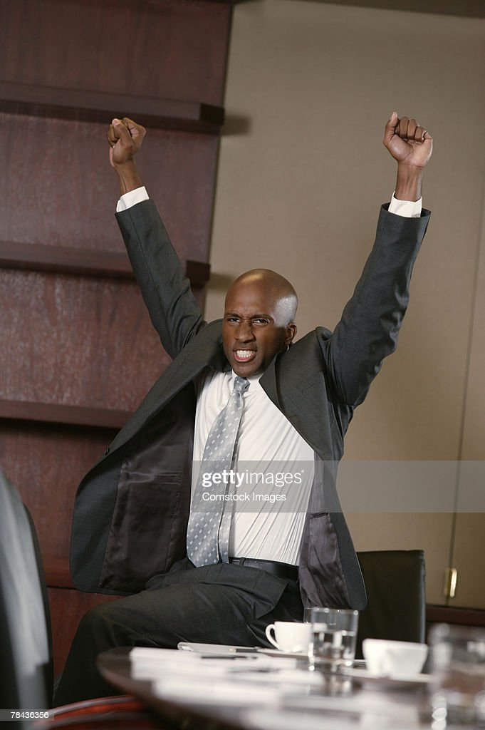 Businessman sitting on conference table cheering : Foto de stock