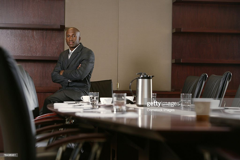 Businessman sitting on conference table : Stockfoto