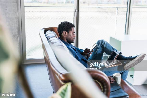 businessman sitting on couch using cell phone and tablet - black blazer stock photos and pictures