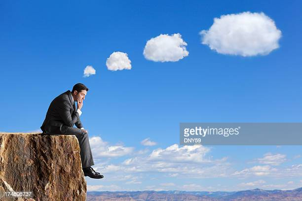 Businessman sitting on edge of cliff thinking