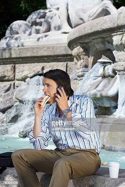 Businessman sitting on edge of fountain eating sandwich whilst on the phone.