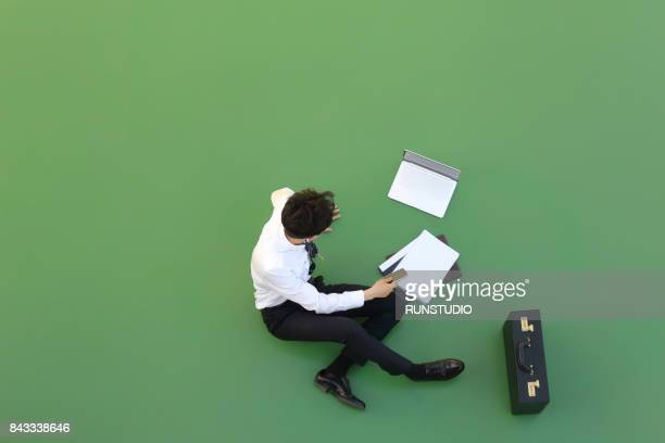 Businessman sitting on floor and using cell phone