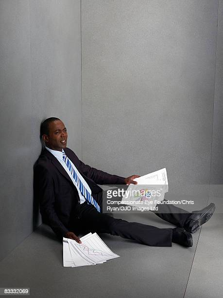 Businessman sitting on floor holding paperwork
