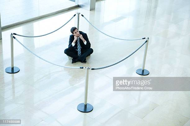 Businessman sitting on floor inside roped off area in lobby