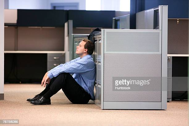 Businessman sitting on floor leaning on file cabinets