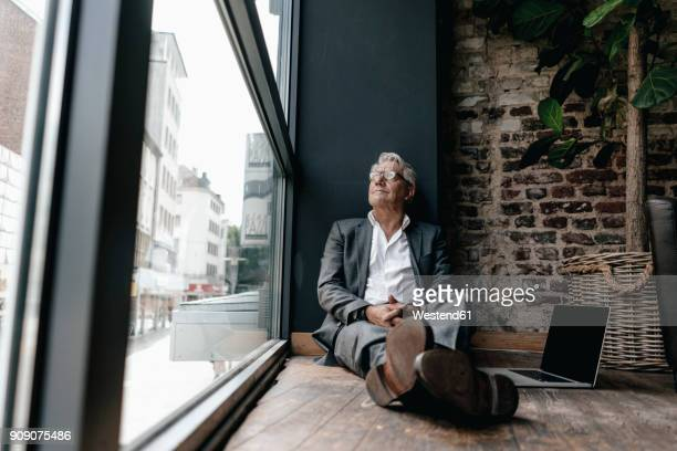 Businessman sitting on floor next to window, taking a break