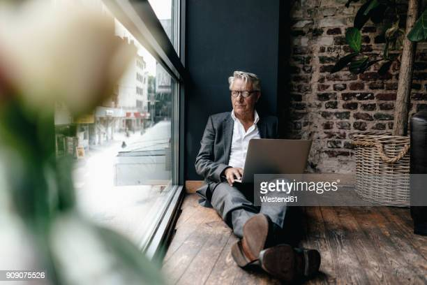 Businessman sitting on floor next to window, using laptop