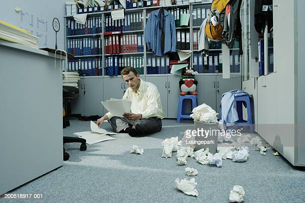 Businessman sitting on floor of messy office